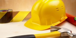 industrial concept with yellow hardhat,hammer and level, selective focus